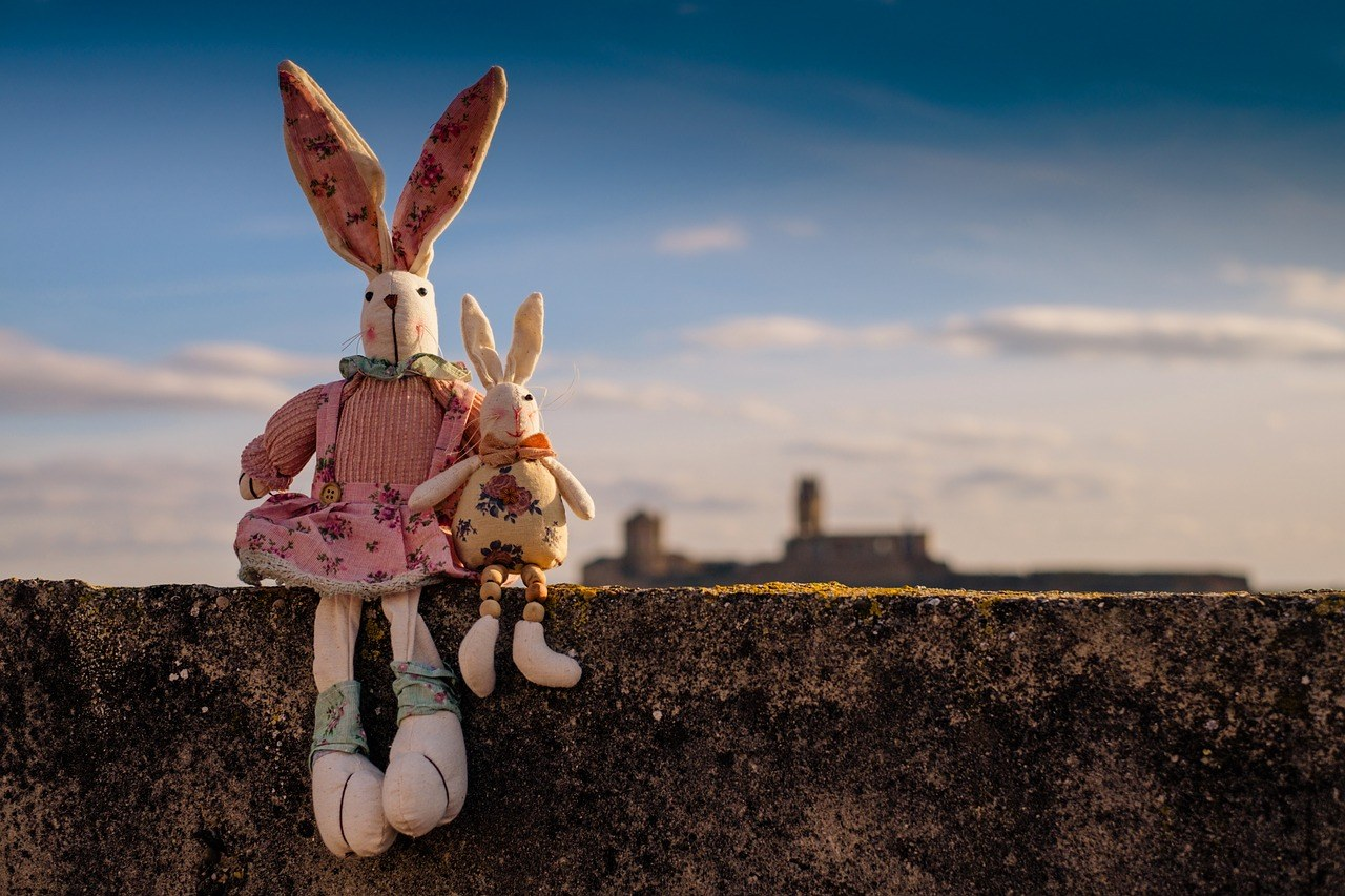 two stuffed animal bunnies sitting on a ledge